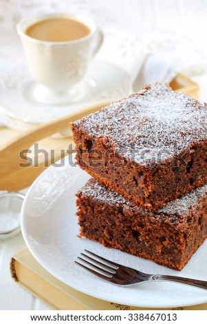 two pieces of plum cake with chocolate and almonds sprinkled with powdered sugar on a white plate