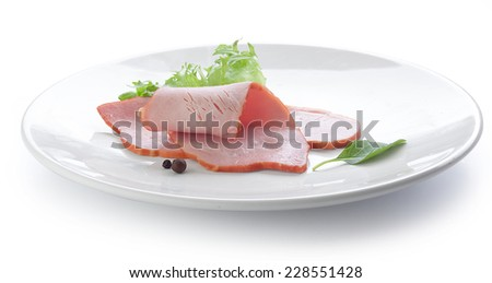 Two pieces of pork loin with fresh green lettuce and basil on the white plate