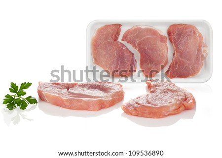 Two pieces of raw pork meat on white background with packed meat in the background