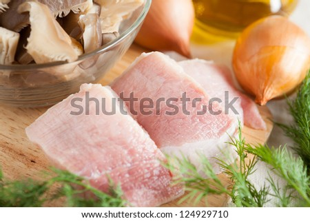 two pieces of raw pork on board closeup