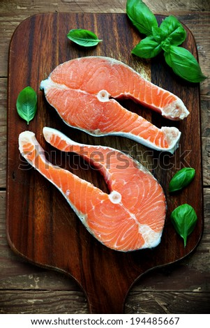 Two pieces of red salmon fillets placed on the wooden cutting board