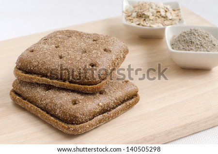 two pieces of rye bread square shape, bran and muesli isolated on wooden background - stock photo