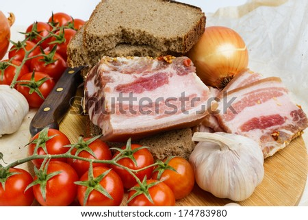 Two pieces of salty bacon with rye bread on a wooden cutting board. - stock photo