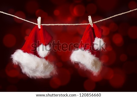 Two pieces of Santa hats are hanging on a string with red defocused lights background - stock photo