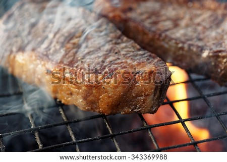 Two pieces of striploin steak on grill, outdoor picnic