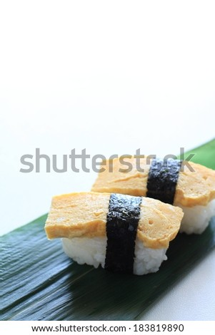 Two pieces of sushi sitting on a green leaf. - stock photo