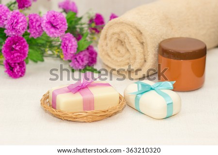 Two pieces of white soap in a basket with  bows , purple flowers , towel and brown jar of cream