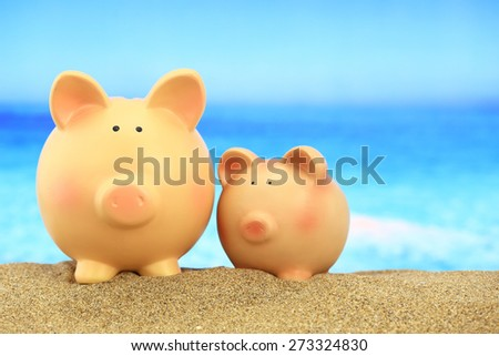 Two piggy banks on the beach