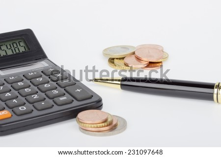 Two piles of coins with calculator and pen on a white background - stock photo