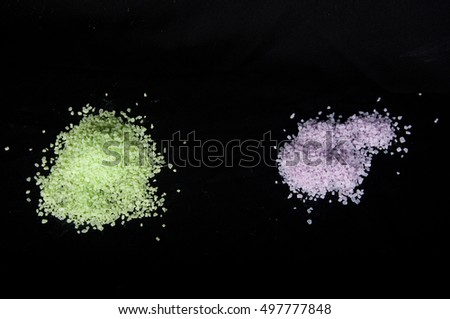 Two piles of light green and purple sea salt grains laying on black background