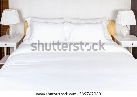 two pillow on bedroom with white bed sheet and lamp - stock photo