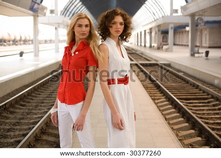 Two pin-up girls on railway station - stock photo