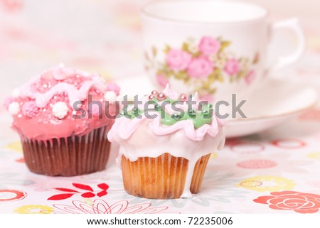 two pink cup cakes and tea cup on backgrounds with flowers.