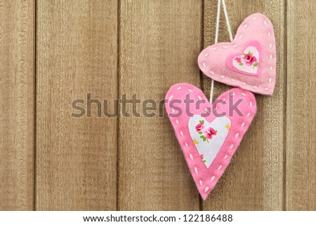 Two pink handmade felt hearts hanging on wooden background. With copy space for a  Valentine's day love message - stock photo
