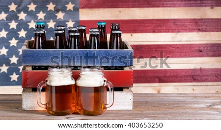 Two pint jars filled with beer, crate with unopen bottle and vintage wooden USA flag in background. Holiday party concept.