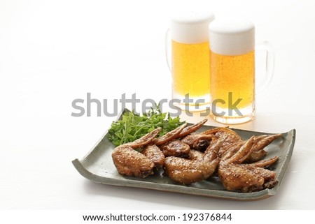 Two pints of beer with chicken wings on a tray. - stock photo