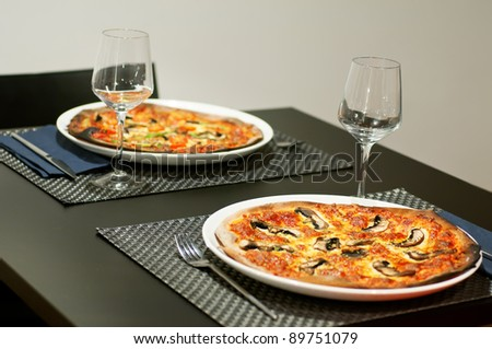 Two pizza. Served at restaurant table. - stock photo