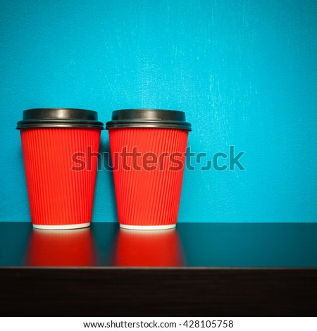 two plastic cups of red on a turquoise background - stock photo