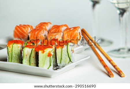 Two plates of salmon and cucumber sushi rolls - stock photo