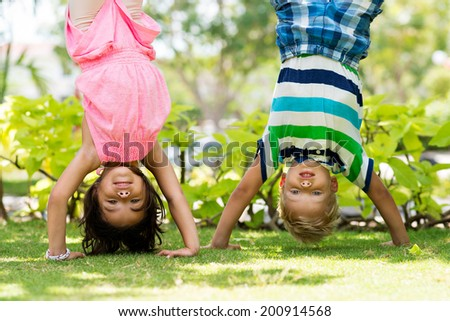 Two playful children standing on their hands in the park - stock photo