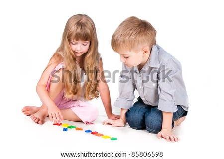 two playing kids with alphabet isolated on white background - stock photo