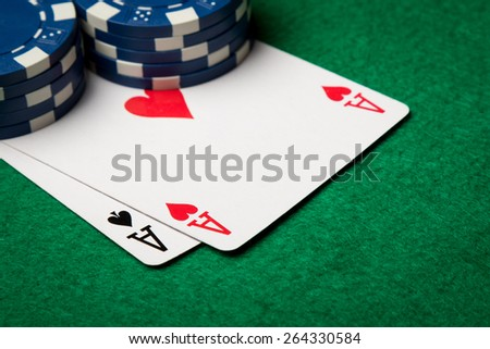 two poker cards, aces, with poker chips in the background - stock photo