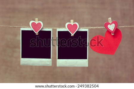 Two polaroid photo frames and heart for valentines day hanging on rope with vintage instagram toning - stock photo