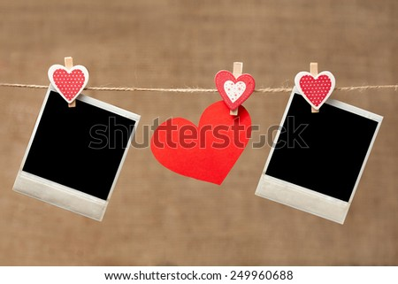 Two polaroid photo frames and heart for valentines day hanging on vintage background - stock photo