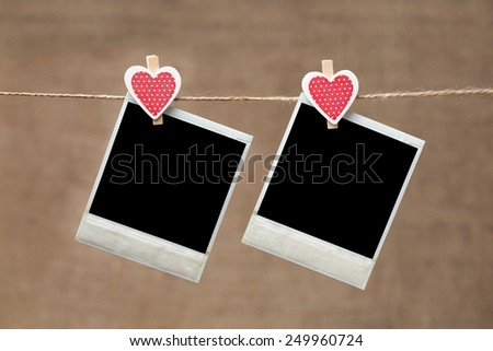 Two polaroid photo frames for valentines day hanging on vintage background - stock photo
