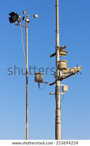 Two Poles with Various Gauges and Devices against a Blue Sky - stock photo