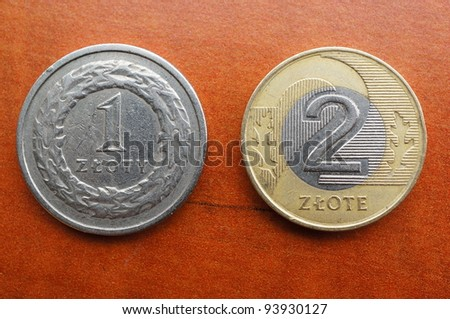 Two polish coins against a wooden background