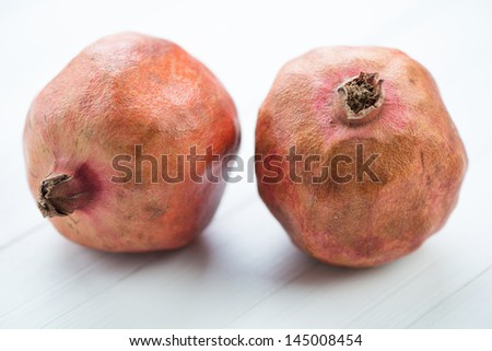 Two pomegranates on white wooden boards, horizontal shot