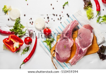 Two pork steak with meat and fresh seasoning spices on white wooden background, top view.