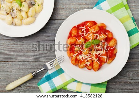 Two portion of gnocchi in tomato sauce and with mushroom with cheese. - stock photo
