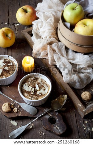 two portions of apple crumble with almonds on rustic wooden table, whole apples and lighted candle - stock photo
