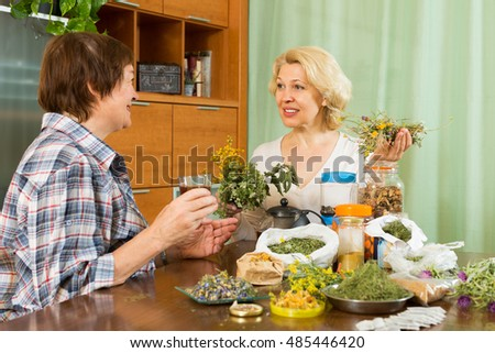 Two positive aged women brewing herbal tea at home with medicinal herbs