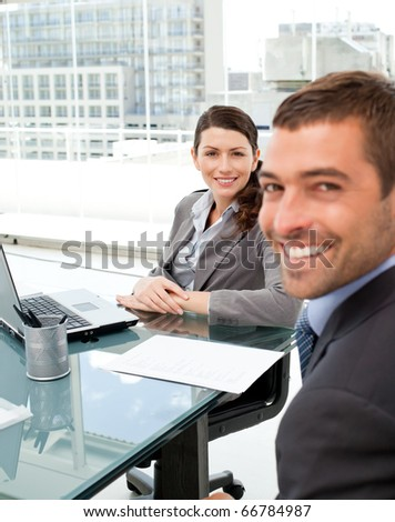 Two positive business people smiling at the camera during an interview