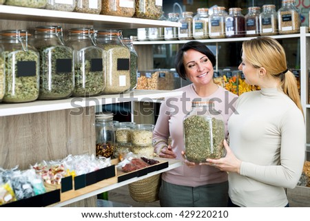 Two positive female customers selecting various herbs in the store with ecological goods - stock photo
