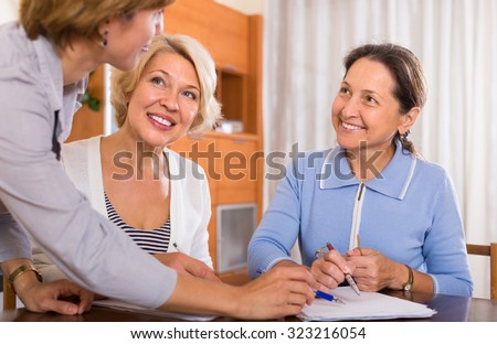 Two positive female pensioners signing documents with public notary