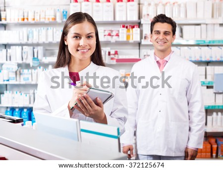 Two positive friendly pharmacists working in modern farmacy