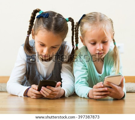 Two positive little girls playing online and browsing web with phones