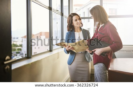 Two positive looking businesswomen standing in an office with large windows looking at each other while discussing some paperwork in a folder with soft sunflare falling through the windows - stock photo