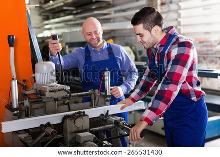 Two positive men in uniform working on machine in PVC shop - stock photo