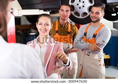 Two postive troubleshooters showing fixed car to cheerful client - stock photo