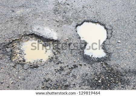 Two potholes that look like footprints in an asphalt road with dirty water in them and loose gravel around them - stock photo