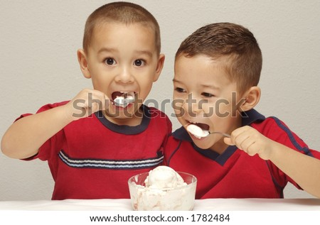 Two preschool brothers enjoy attacking a bowl of strawberry-cheesecake ice cream