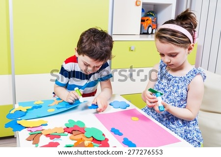 Two preschool child create a picture with foam shapes