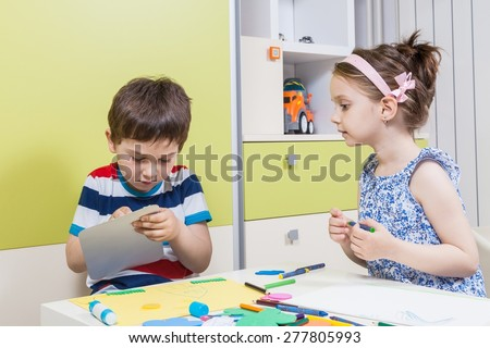 Two preschool child working for homework received from kindergarten
