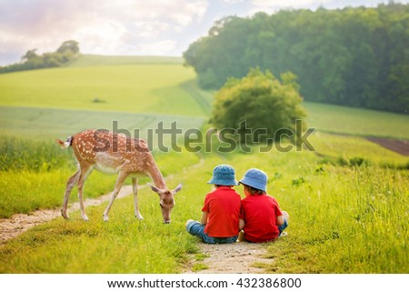 Two preschool children, sitting in the rural, contemplating little foe, eating grass, springtime - stock photo