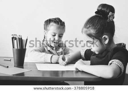two preschool girls are drawing at the table - stock photo